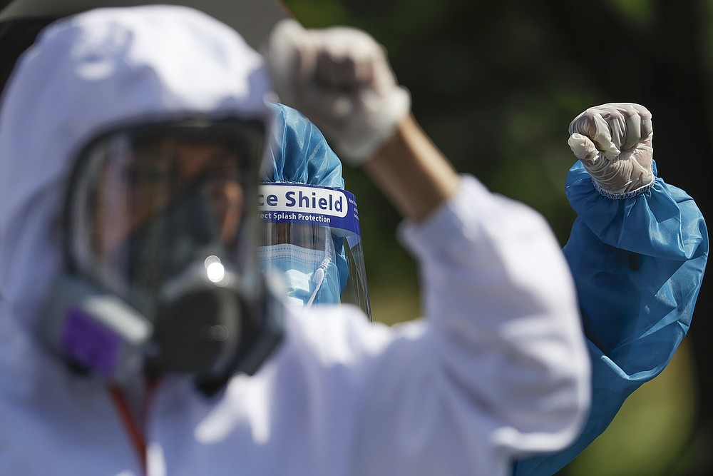 Health workers in protective suits clench fists during a protest against the State of the Nation Address (SONA) by Philippine President Rodrigo Duterte on Monday, July 27, 2020 in Metro Manila, Philippines. Hundreds of protesters marched, staged motorcades and held a rally against a new anti-terror law and other issues Monday in the Philippine capital despite police threats of arrests ahead of the president's annual state of the nation speech. (AP Photo/Aaron Favila)