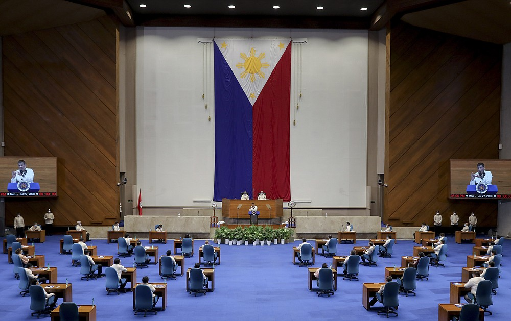 In this photo provided by the Malacanang Presidential Photographers Division, Philippine President Rodrigo Duterte, center, delivers his State of the Nation Address (SONA) attended by some representatives, senators and cabinet officials to prevent the spread of COVID19 at the House of Representative in Metro Manila, Philippines, Monday, July 27, 2020. (Simeon Celi Jr./Malacanang Presidential Photographers Division via AP)