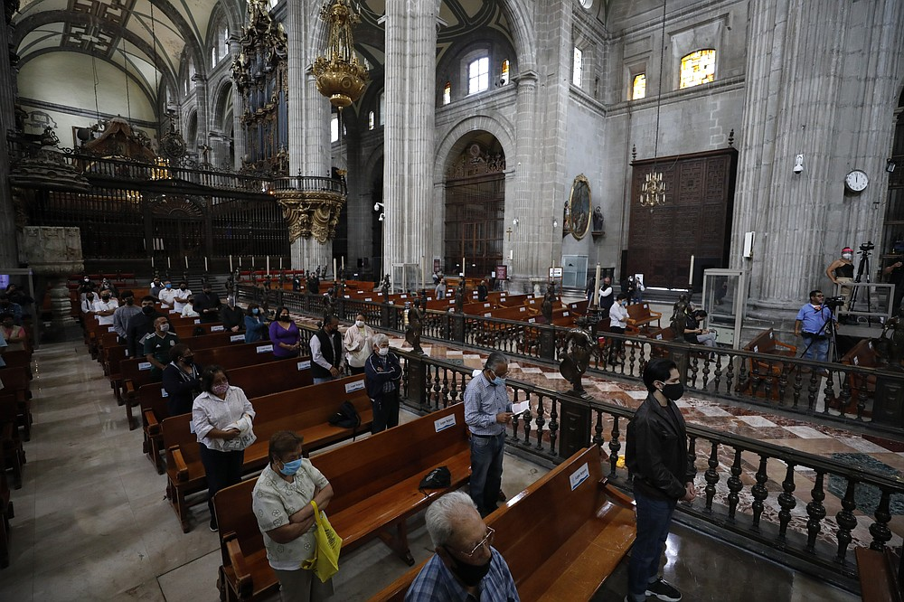 Catholic faithful, wearing masks and practicing distancing during the coronavirus pandemic, attend Mass at Metropolitan Cathedral in Mexico City.