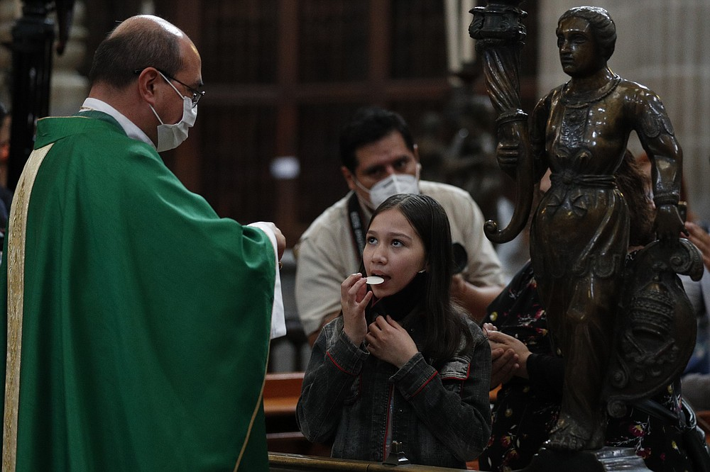 A young woman lowers her mask to take the Communion wafer, as Auxiliary Bishop Salvador Gonzalez distributes wafers to Catholic faithful waiting near their seats, as the the Metropolitan Cathedral reopened for public services amidst the ongoing coronavirus pandemic, in Mexico City, Sunday, July 26, 2020. (AP Photo/Rebecca Blackwell)