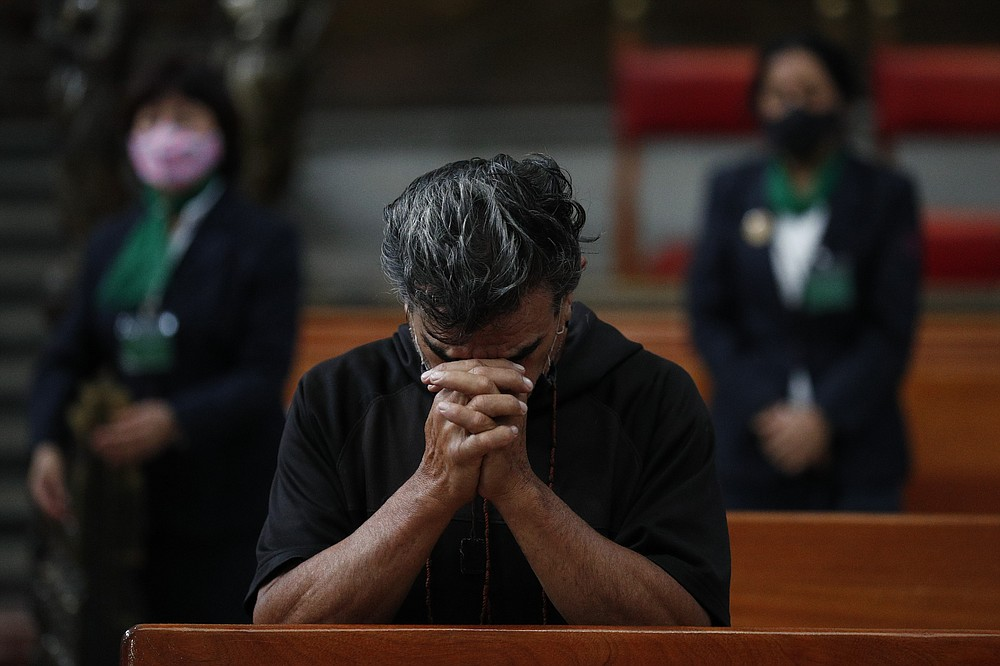 A man prays during Catholic Mass, on the first day the Metropolitan Cathedral reopened for public services amidst the ongoing coronavirus pandemic, in Mexico City, Sunday, July 26, 2020. (AP Photo/Rebecca Blackwell)