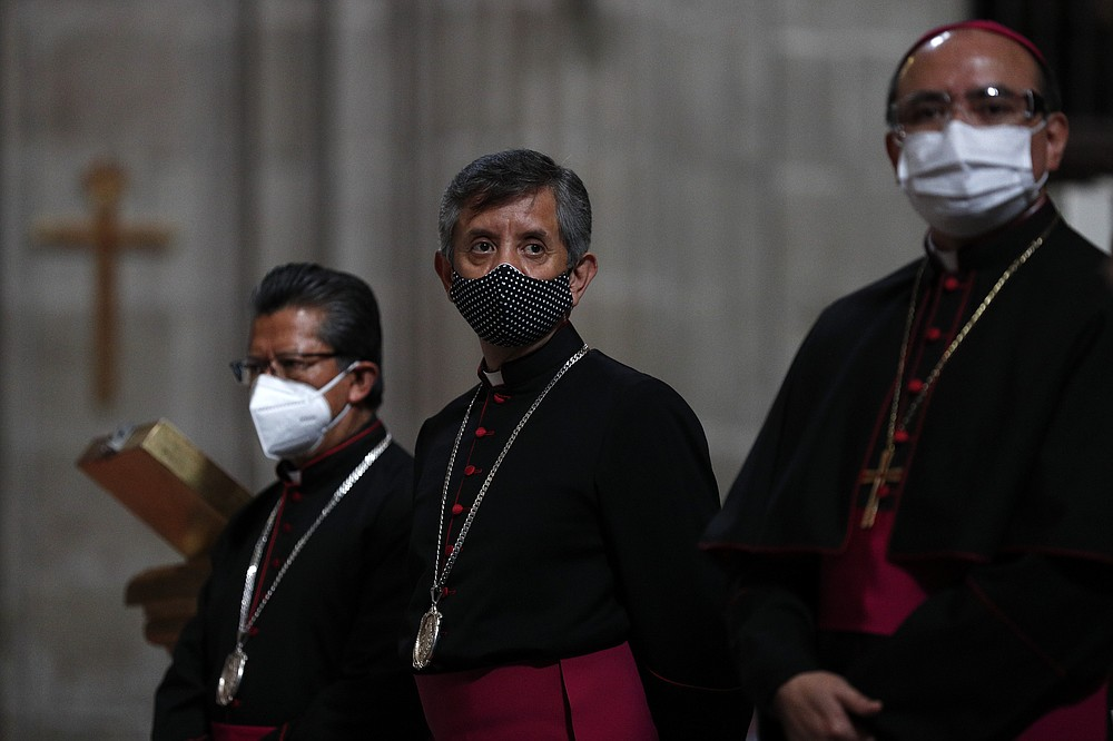 Catholic priests stand inside the Metropolitan Cathedral ahead of the first Mass open to the public amidst the ongoing coronavirus pandemic, in Mexico City, Sunday, July 26, 2020. (AP Photo/Rebecca Blackwell)