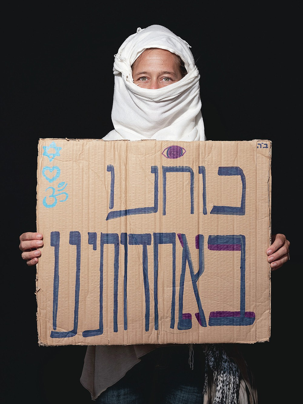 """Michal Esther Katzir, 35, poses for a photo during a protest against Israel's Prime Minister Benjamin Netanyahu, outside his residence in Jerusalem, Thursday, July 23, 2020. Hebrew on sign reads """"Our strength is in our unity"""". The wave of colorful and combative demonstrations against Netanyahu and his perceived failure to handle the country's deepening economic crisis have been characterized by youth. With flags, facemasks, drums, placards and an assortment of props, thousands have been taking to the streets to demand change in a variety of unique ways. (AP Photo/Oded Balilty)"""