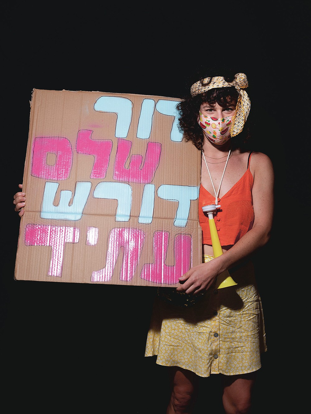 """Kalanit Sharon, 31, poses for a photo during a protest against Israel's Prime Minister Benjamin Netanyahu, outside his residence in Jerusalem, Thursday, July 23, 2020. Hebrew on sign reads """"An entire generation demands for future"""". The wave of colorful and combative demonstrations against Netanyahu and his perceived failure to handle the country's deepening economic crisis have been characterized by youth. With flags, facemasks, drums, placards and an assortment of props, thousands have been taking to the streets to demand change in a variety of unique ways. (AP Photo/Oded Balilty)"""