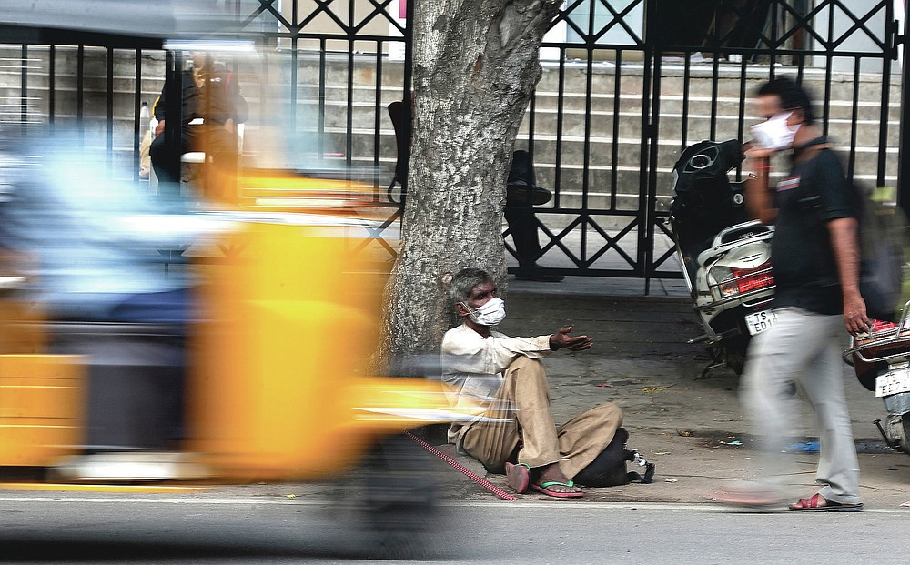 An Indian man wearing mask as a precaution against the coronavirus seeks alms at a street in Hyderabad, India, Monday, July 27, 2020. India is the third hardest-hit country by the pandemic in the world after the United States and Brazil. (AP Photo/Mahesh Kumar A.)