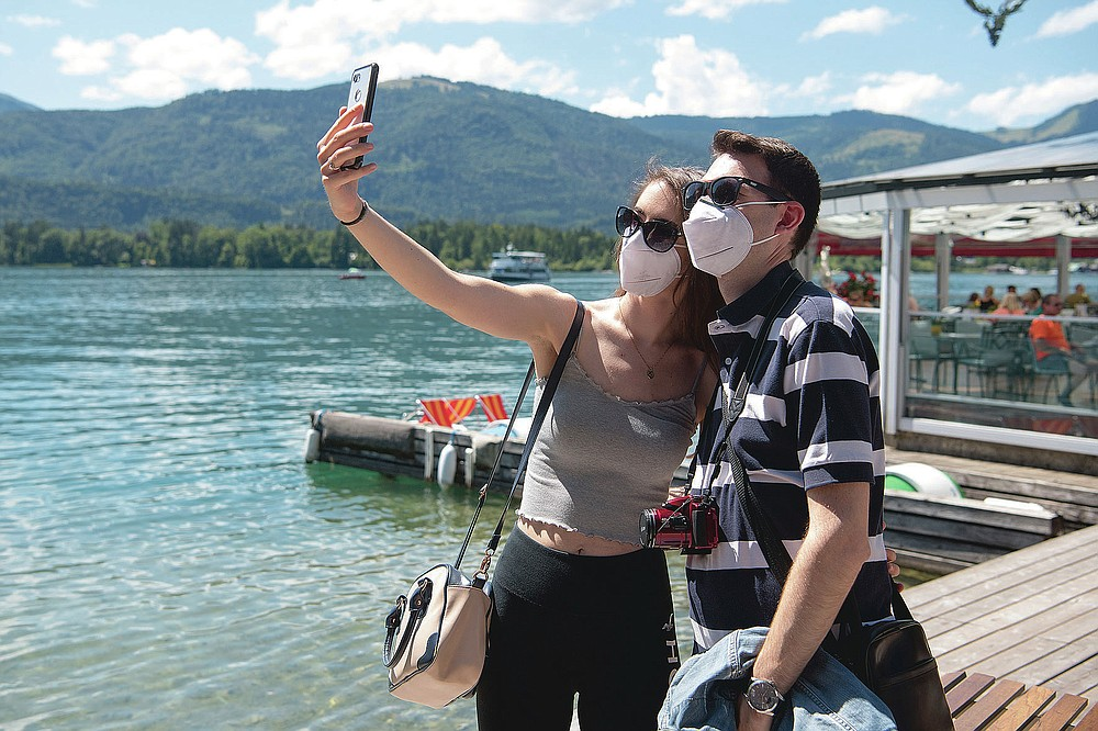 A couple make selfies at the lake side in St. Wolfgang, Austria, Monday, July 27, 2020. More than 50 corona tests in the small community of St. Wolfgang in the Salzkammergut have been positive in the past few days. Young interns in tourism companies are particularly affected, but at least one holiday guest has also been tested positive. St. Wolfgang is the most important holiday resort in Upper Austria.(AP Photo/Kerstin Joensson)