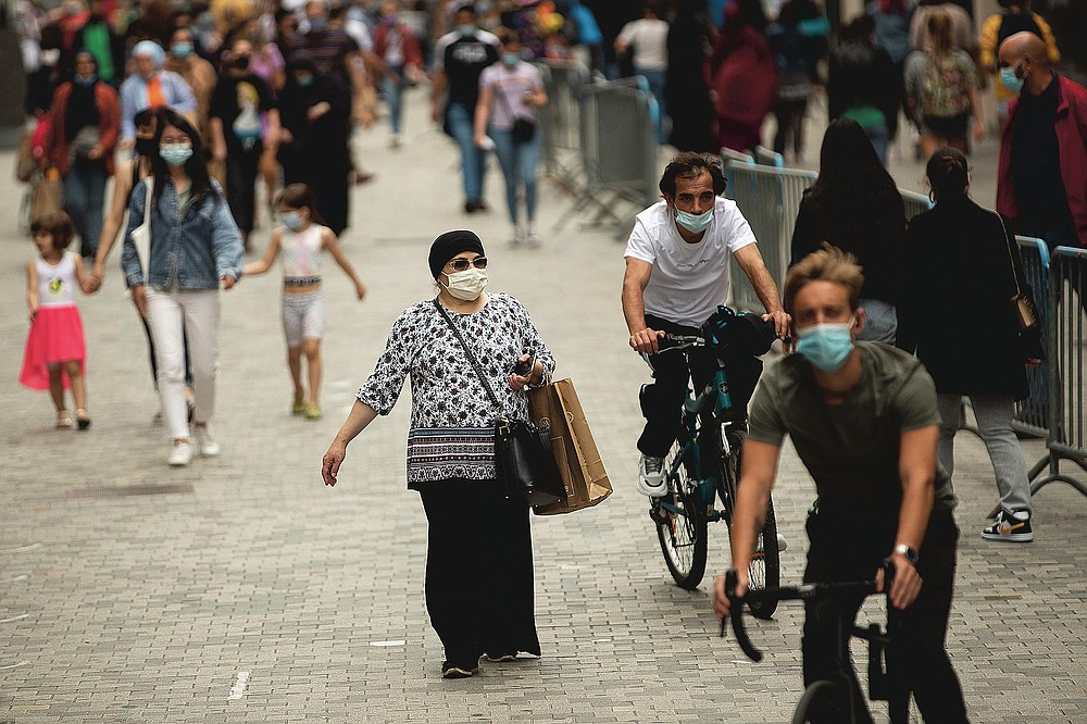 People, wearing masks to protect against the spread of coronavirus, walk along Neuve commercial street at downtown Brussels, Monday, July 27, 2020. Belgian Prime Minister Sophie Wilmes unveiled Monday a new set of drastic social distancing measures aimed at avoiding a new general lockdown amid a surge of COVID-19 infections. (AP Photo/Francisco Seco)