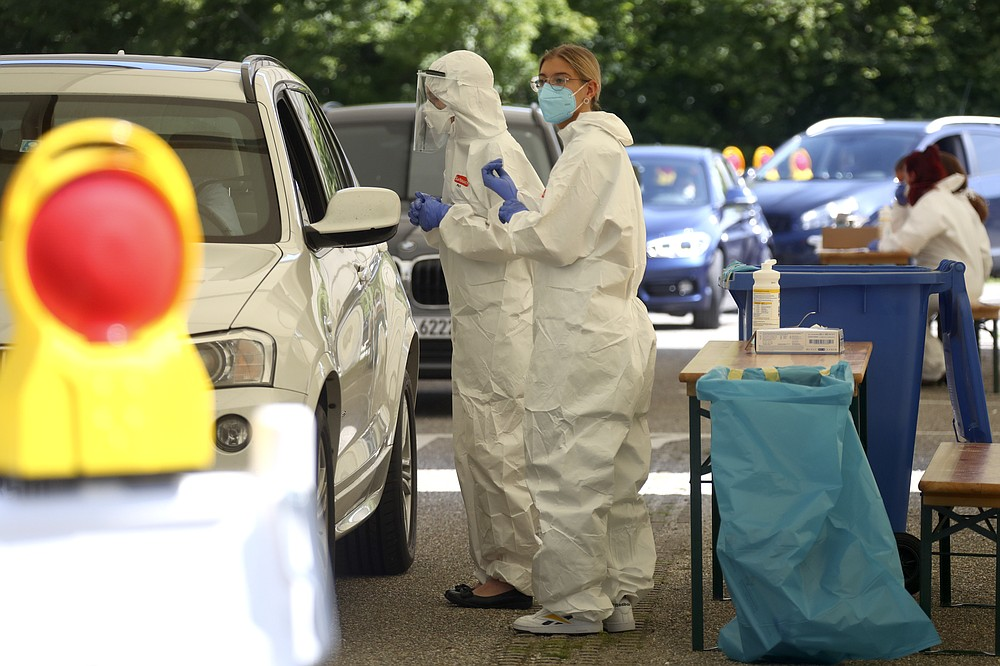 Health workers collect samples at a makeshift COVID-19 testing station in Mamming, Germany, Tuesday July 28, 2020. After a local coronavirus outbreak on the cucumber farm premises, state authorities have quarantined the entire farm and its workers. (AP Photo/Matthias Schrader)