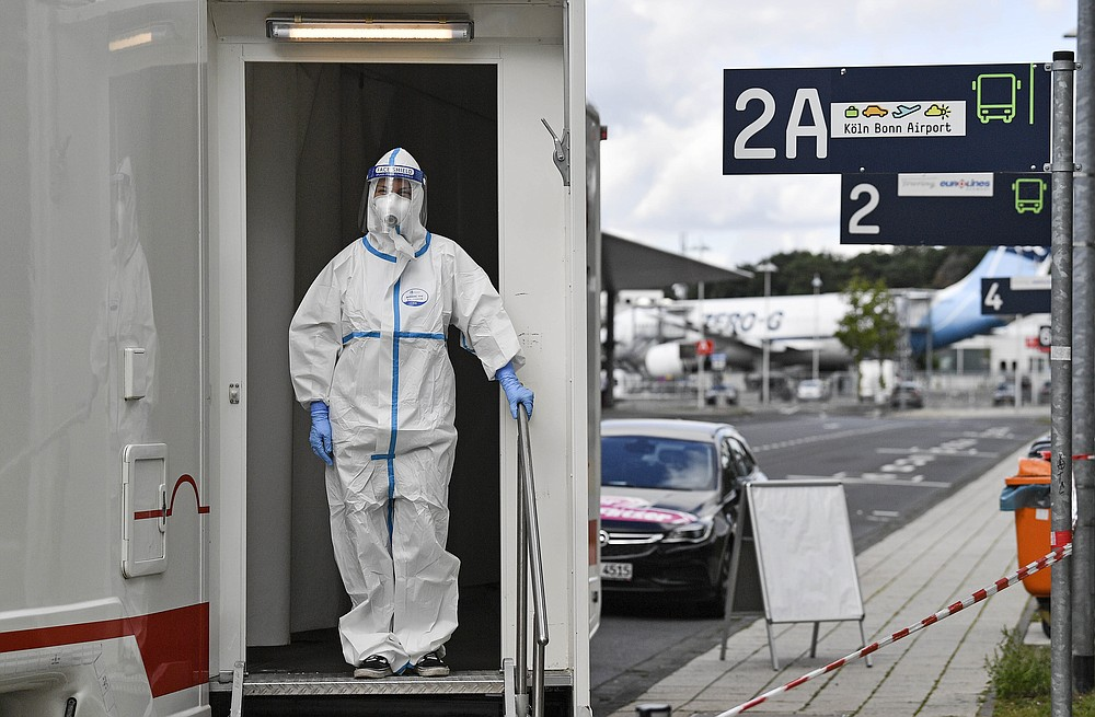 Medical staff wait for travelers to take COVID-19 tests from arriving passengers at the airport in Cologne, Germany, Tuesday, July 28, 2020. New test centers for coronavirus are established at German airports due to the pandemic and free corona tests are given for returnees from countries designated as risk areas. (AP Photo/Martin Meissner)