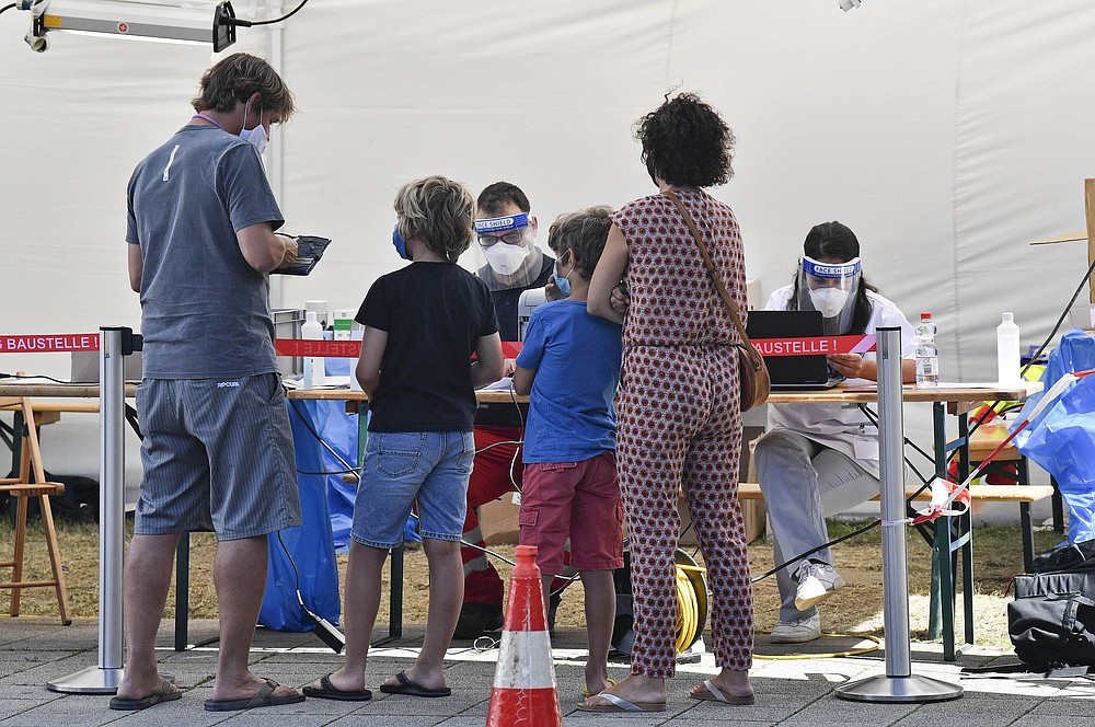Travelers arrive at a test station to make a COVID-19 test at the airport in Cologne, Germany, Tuesday, July 28, 2020. New test centers for coronavirus are established at German airports due to the pandemic and free corona tests are given for returnees from countries designated as risk areas.  (AP Photo/Martin Meissner)