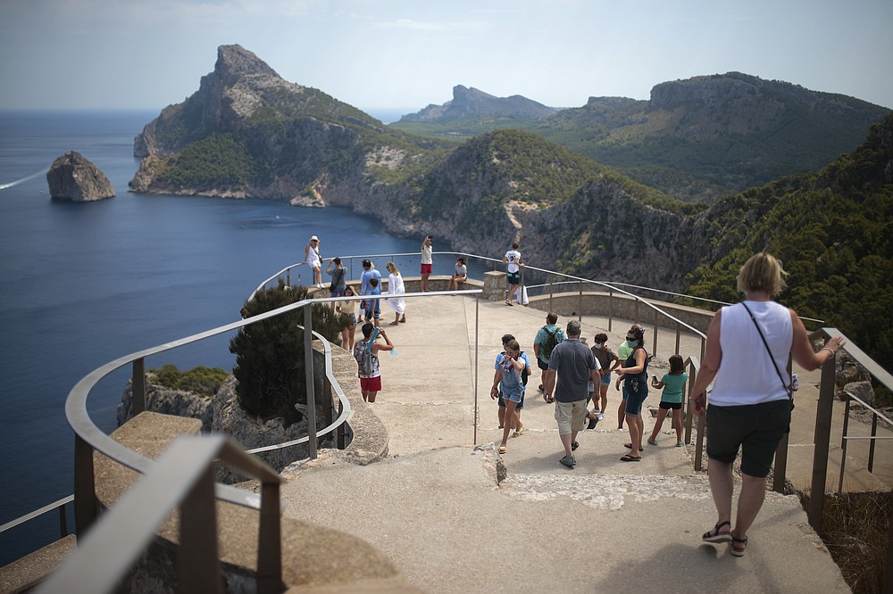 Tourists visit a viewpoint in Pollença, in the Balearic Island of Mallorca, Spain, Tuesday, July 28, 2020. Britain has put Spain back on its unsafe list and announced Saturday that travelers arriving in the U.K. from Spain must now quarantine for 14 days. (AP Photo/Joan Mateu)