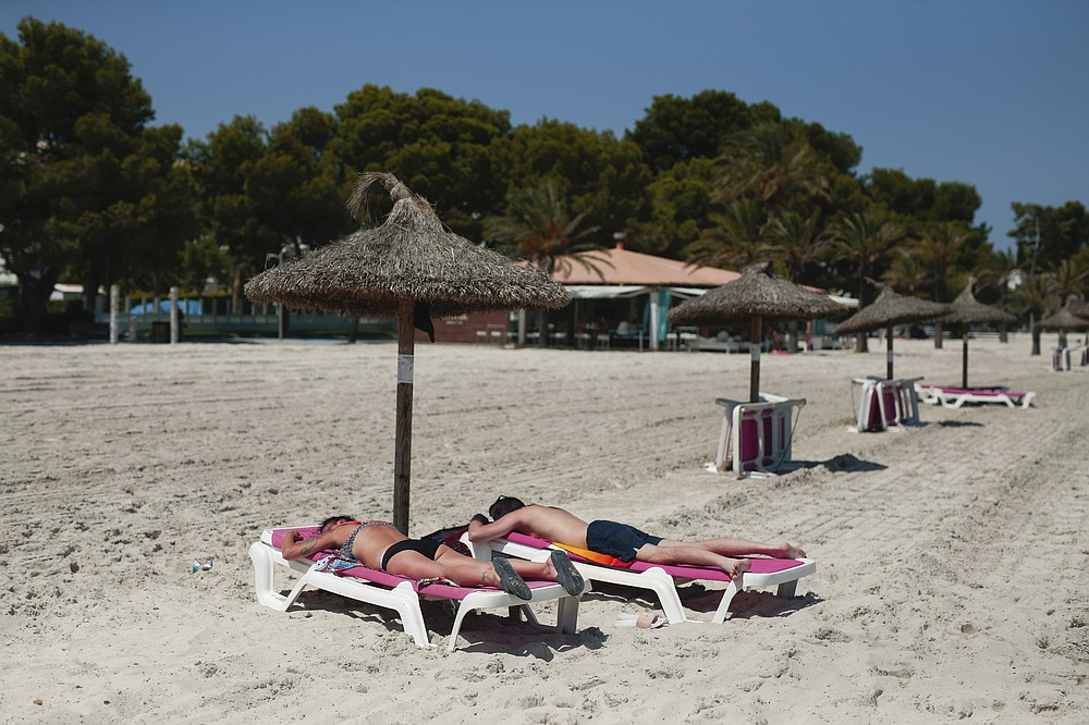 Sunbathers enjoy the beach in Alcúdia, in the Balearic Island of Mallorca, Spain, Tuesday, July 28, 2020. The U.K. government's recommendation against all but essential travel to the whole of Spain means that all travelers arriving in Britain from that country will have to undergo a 14-day quarantine. (AP Photo/Joan Mateu)