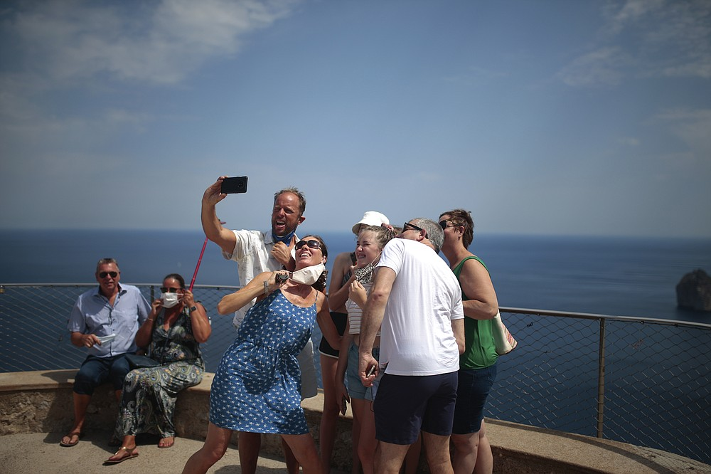 Tourists visiting from the UK take a selfie at a viewpoint in Pollença, in the Balearic Island of Mallorca, Spain, Tuesday, July 28, 2020. Britain has put Spain back on its unsafe list and announced Saturday that travelers arriving in the U.K. from Spain must now quarantine for 14 days. (AP Photo/Joan Mateu)