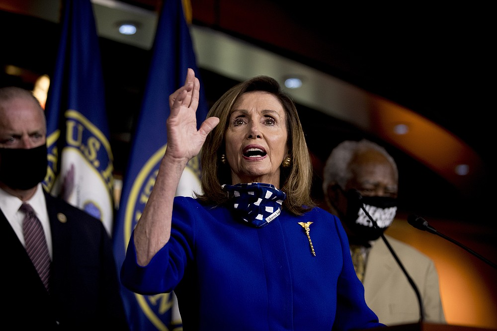 House Speaker Nancy Pelosi of Calif., accompanied by Rep. Dan Kildee, D-Mich., left, and Rep. Danny Davis, D-Ill., right, speaks at a news conference on Capitol Hill in Washington, Friday, July 24, 2020, on the extension of federal unemployment benefits. (AP Photo/Andrew Harnik)