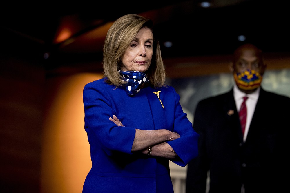 House Speaker Nancy Pelosi of Calif., left, accompanied by Rep. Dwight Evans, D-Pa., right, listens to a question from a reporter during a news conference on Capitol Hill in Washington, Friday, July 24, 2020, on the extension of federal unemployment benefits. (AP Photo/Andrew Harnik)