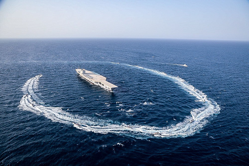 """In this photo released Tuesday, July 28, 2020, by Sepahnews, Revolutionary Guard's speed boats circle around a replica aircraft carrier during a military exercise. Iran's paramilitary Revolutionary Guard fired a missile from a helicopter targeting the mock-up aircraft carrier in the strategic Strait of Hormuz according to footage aired on state television on Tuesday. Iranian commandos also fast-roped down from a helicopter onto the replica in the footage from the exercise called """"Great Prophet 14."""" The drill appears aimed at threatening the U.S. amid tensions between Tehran and Washington. (Sepahnews via AP)"""