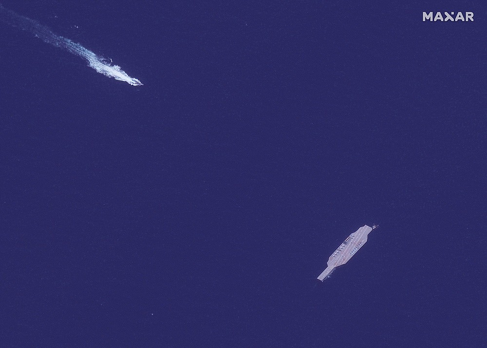 In this July 26, 2020, satellite photo provided on July 27, by Maxar Technologies, an Iranian fast boat, top left, approaches a mockup aircraft carrier built by Iran in the Strait of Hormuz. Satellite photographs released Monday, July 27, showed Iran has moved the aircraft carrier out to sea likely for naval drills amid heightened tensions between Tehran and the U.S. (Maxar Technologies via AP)