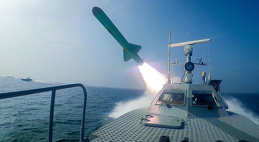 """In this photo released Tuesday, July 28, 2020, by Sepahnews, a Revolutionary Guard's speed boat fires a missile during a military exercise. Iranian commandos also fast-roped down from a helicopter onto a replica of an aircraft carrier in the exercise called """"Great Prophet 14."""" The drill appears aimed at threatening the U.S. amid tensions between Tehran and Washington. (Sepahnews via AP)"""