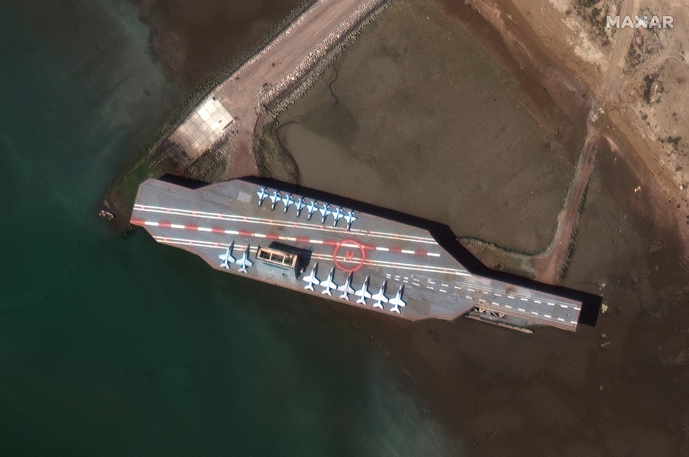In this Feb. 15, 2020, satellite photo provided on July 27, 2020, by Maxar Technologies, a mockup aircraft carrier built by Iran is seen at Bandar Abbas, Iran, before being put to sea. Satellite photographs released Monday, July 27, showed Iran has moved the aircraft carrier out to sea likely for naval drills amid heightened tensions between Tehran and the U.S. (Maxar Technologies via AP)