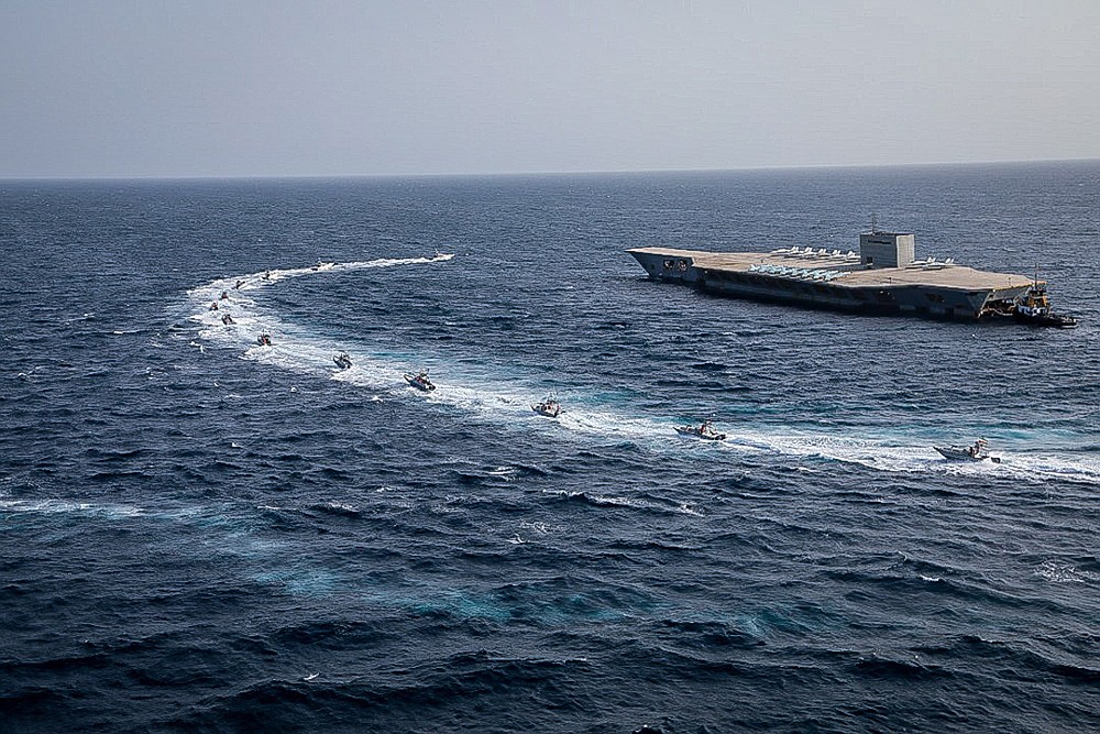 """In this photo released Tuesday, July 28, 2020, by Sepahnews, Revolutionary Guard's speed boats circle around a replica aircraft carrier during a military exercise. Iran's paramilitary Revolutionary Guard has fired a missile from a helicopter targeting the mock-up aircraft carrier in the strategic Strait of Hormuz according to footage aired on state television on Tuesday. Iranian commandos also fast-roped down from a helicopter onto the replica in the footage from the exercise called """"Great Prophet 14."""" The drill appears aimed at threatening the U.S. amid tensions between Tehran and Washington. (Sepahnews via AP)"""