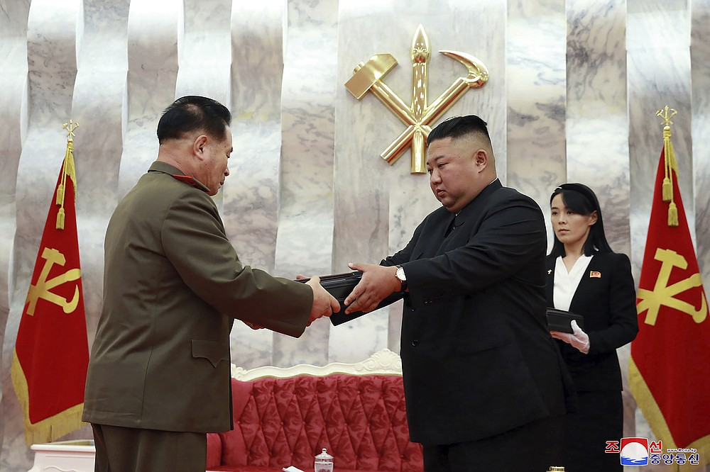 """In this Sunday, July 26, 2020, photo released by the North Korean government, North Korean leader Kim Jong Un, center, hands over a """"Paektusan"""" commemorative pistol to a senior military official during a ceremony in Pyongyang, North Korea. At right is Kim's powerful sister Kim Yo Jong. Independent journalists were not given access to cover the event depicted in this image distributed by the North Korean government. The content of this image is as provided and cannot be independently verified. Korean language watermark on image as provided by source reads: """"KCNA"""" which is the abbreviation for Korean Central News Agency. (Korean Central News Agency/Korea News Service via AP)"""