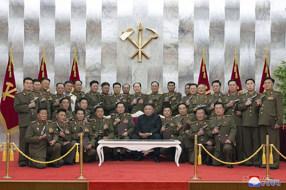 """In this Sunday, July 26, 2020, photo released by the North Korean government, North Korean leader Kim Jong Un, center, poses for a photo with senior military officials holding """"Paektusan"""" commemorative pistols they received from Kim during a ceremony in Pyongyang, North Korea. Independent journalists were not given access to cover the event depicted in this image distributed by the North Korean government. The content of this image is as provided and cannot be independently verified. Korean language watermark on image as provided by source reads: """"KCNA"""" which is the abbreviation for Korean Central News Agency. (Korean Central News Agency/Korea News Service via AP)"""