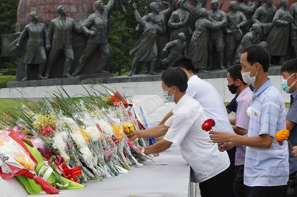 """People lay flowers  the statues of former North Korean leaders Kim Il Sung and Kim Jong Il on the occasion of the 67th anniversary of the end of the Korean War, which the country celebrates as the day of """"victory in the fatherland liberation war"""" in Pyongyang, Monday, July 27, 2020. (AP Photo/Jon Chol Jin)"""