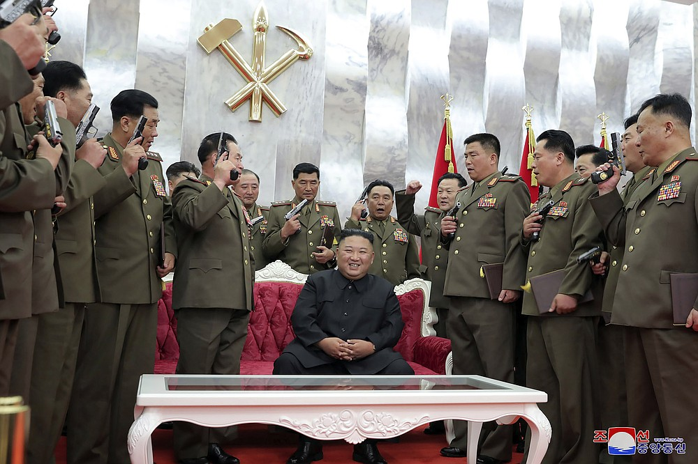 """In this Sunday, July 26, 2020, photo released by the North Korean government, North Korean leader Kim Jong Un, sitting center,  is surrounded by senior military officials holding """"Paektusan"""" commemorative pistols they received from Kim during a ceremony in Pyongyang, North Korea. Independent journalists were not given access to cover the event depicted in this image distributed by the North Korean government. The content of this image is as provided and cannot be independently verified. Korean language watermark on image as provided by source reads: """"KCNA"""" which is the abbreviation for Korean Central News Agency. (Korean Central News Agency/Korea News Service via AP)"""