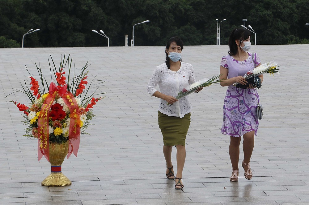 """People visit the statues of former North Korean leaders Kim Il Sung and Kim Jong Il to lay flowers on the occasion of the 67th anniversary of the end of the Korean War, which the country celebrates as the day of """"victory in the fatherland liberation war"""" in Pyongyang, Monday, July 27, 2020. (AP Photo/Jon Chol Jin)"""