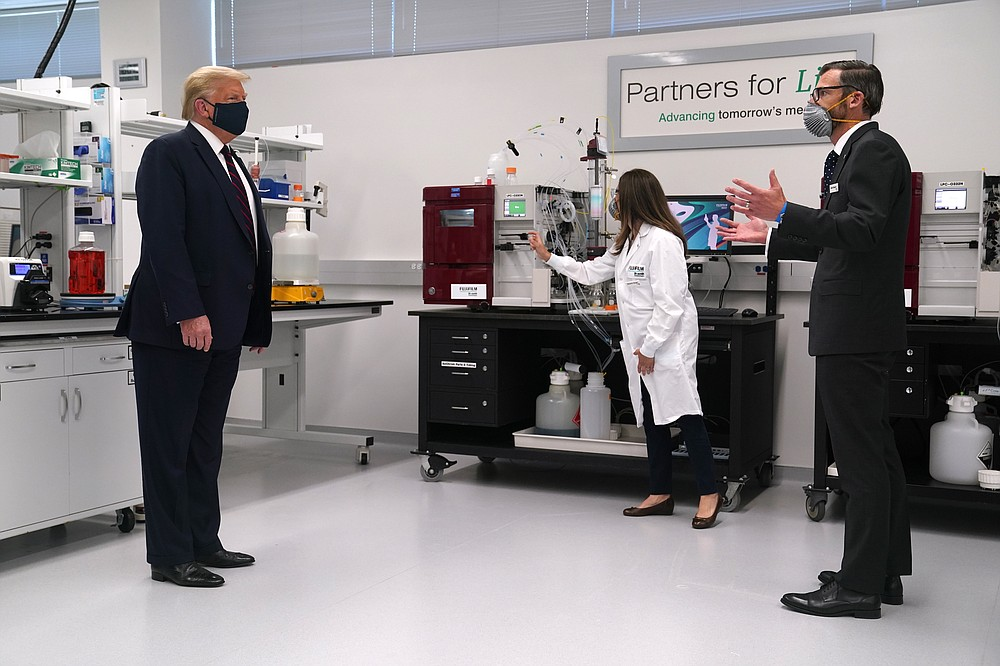 Fujifilm Diosynth Biotechnologies CEO Martin Meeson, right, speaks as President Donald Trump wears a face mask as he participates in a tour of Bioprocess Innovation Center at Fujifilm Diosynth Biotechnologies, Monday, July 27, 2020, in Morrisville, N.C. (AP Photo/Evan Vucci)