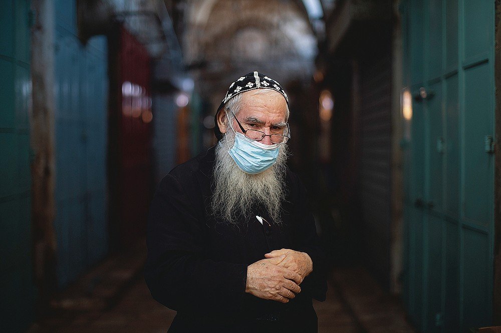 """Syrian Orthodox priest, Shimon Jan, 70, poses for a portrait wearing his protective face mask in the alleys of Jerusalem's Old City, on July 21, 2020. Jan says """"I'm advising to everyone to wear face masks not only because of the law also because life is the most important thing"""". (AP Photo/Oded Balilty)"""