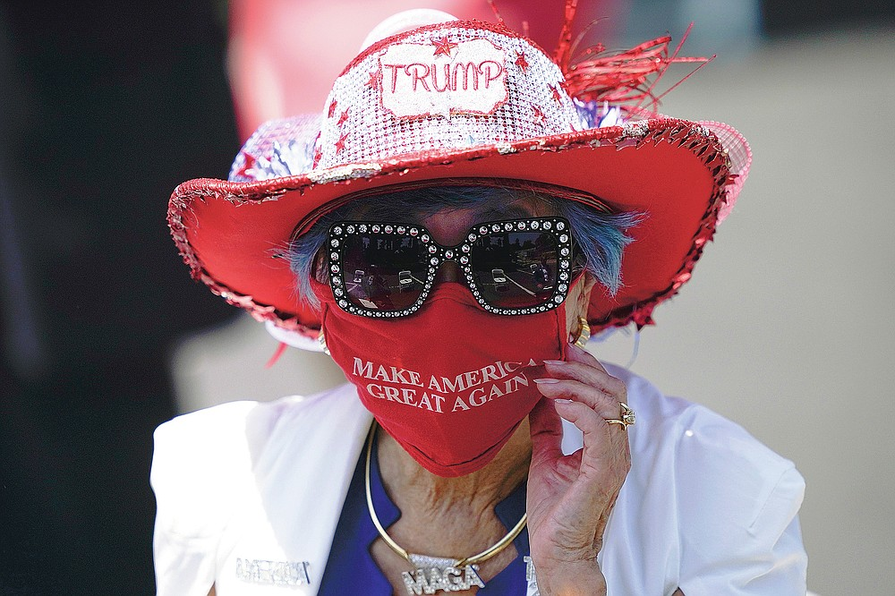 Betty Chu adjusts her face mask before listening to Secretary of State Mike Pompeo speak at the Richard Nixon Presidential Library in Yorba Linda, Calif., on July 23, 2020. (AP Photo/Ashley Landis, Pool)