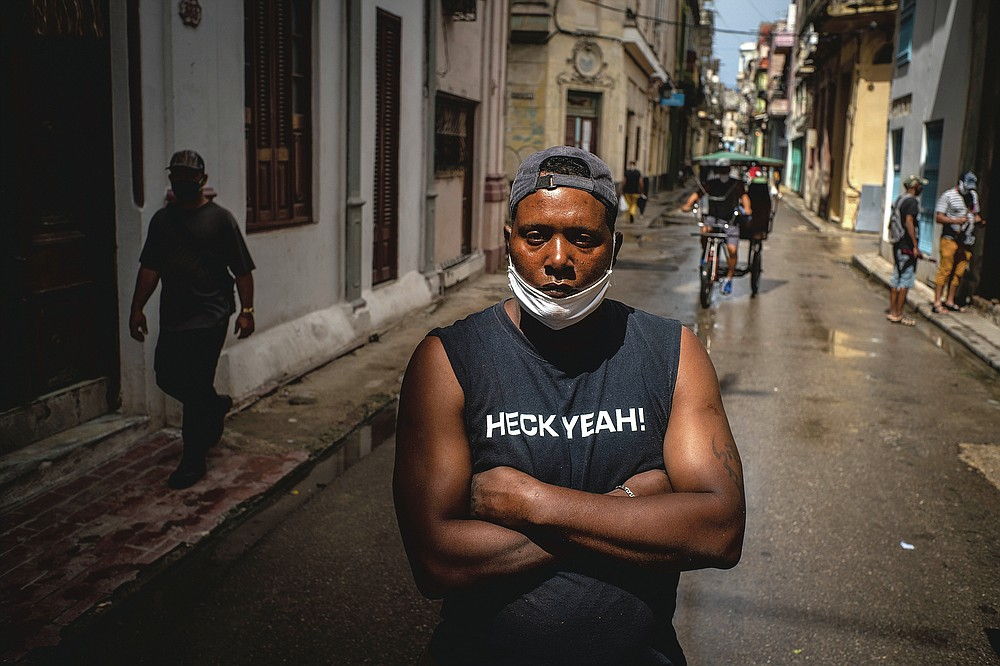 """Street Vendor Maikel Chirino, 38, wears a protective face mask in Old Havana, Cuba on July 22, 2020. """"The advice I give all people is to continue using the mask while they can use it because that would be good for the whole world and for this disease not to spread as much."""" (AP Photo/Ramon Espinosa)"""