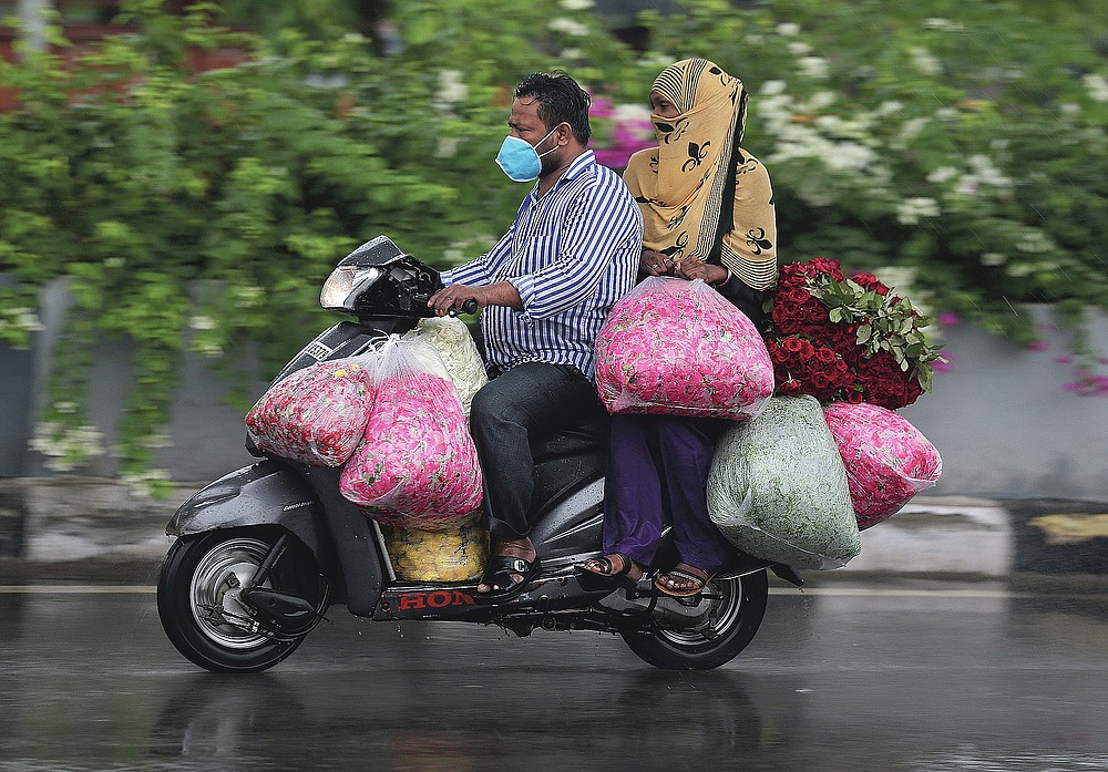 An Indian man wearing face mask transports flowers in the rain in Hyderabad, India on July 23, 2020. India receives its monsoon rains from June to September. (AP Photo/Mahesh Kumar A.)