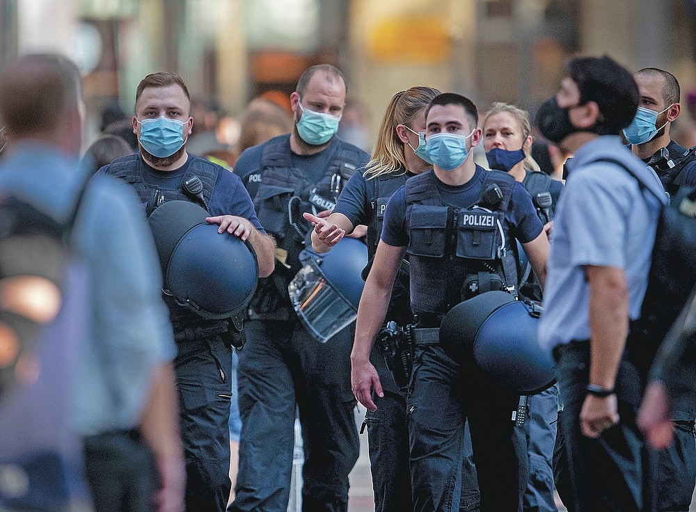 German police officers wear face mask as they walk through the central train station in Frankfurt, Germany, on July 22, 2020. (AP Photo/Michael Probst)