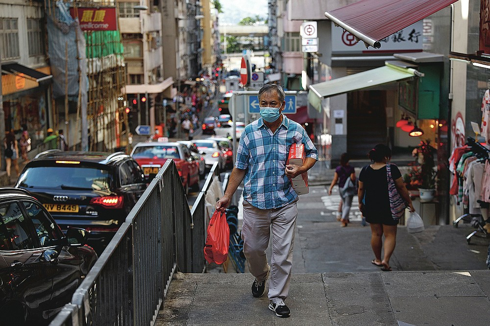 """A man wears a face mask while walking along a street in Hong Kong on July 22, 2020. Hong Kong is facing a """"critical stage"""" in its fight against COVID-19, and the government is extending anti-virus measures. (AP Photo/Kin Cheung)"""