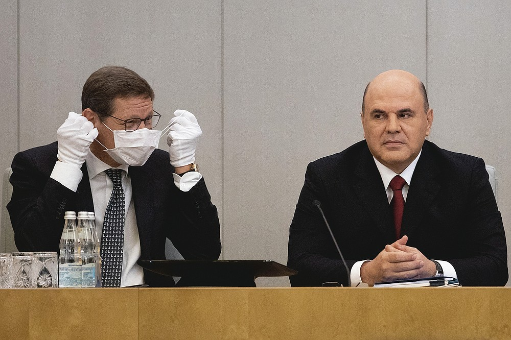 Russian State Duma deputy speaker Alexander Zhukov, left, takes off his face mask as he sits next to Russian Prime Minister Mikhail Mishustin prior to a session of the State Duma, the Lower House of the Russian Parliament on July 22, 2020.  (AP Photo/Alexander Zemlianichenko)