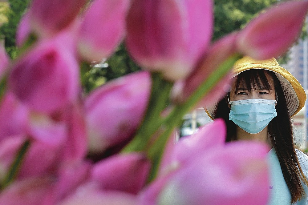 A woman wears a face mask as she walks by lotus flowers on sale on a street in Beijing, on July 22, 2020. (AP Photo/Andy Wong)