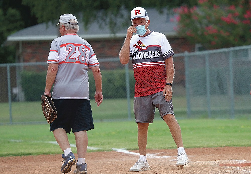 Rick McAll, 73, wears a face mask as he stands on first base after hitting a single during a senior's softball game in Richardson, Texas, on July 21, 2020. (AP Photo/LM Otero)