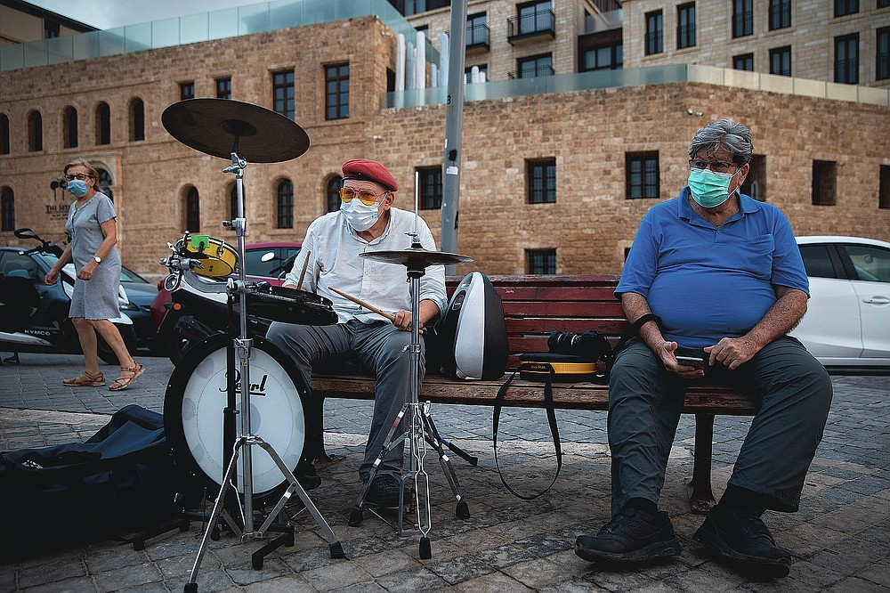 Alex Olshansky, left, wears a protective face mask while playing drums in Tel Aviv, Israel, Monday, July 20, 2020. (AP Photo/Oded Balilty)