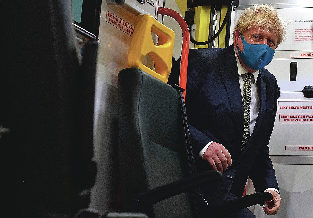 Britain's Prime Minister Boris Johnson wears a face mask as he boards an ambulance during a visit to the headquarters of the London Ambulance Service NHS Trust in London on July 13, 2020. (Ben Stansall/Pool via AP)