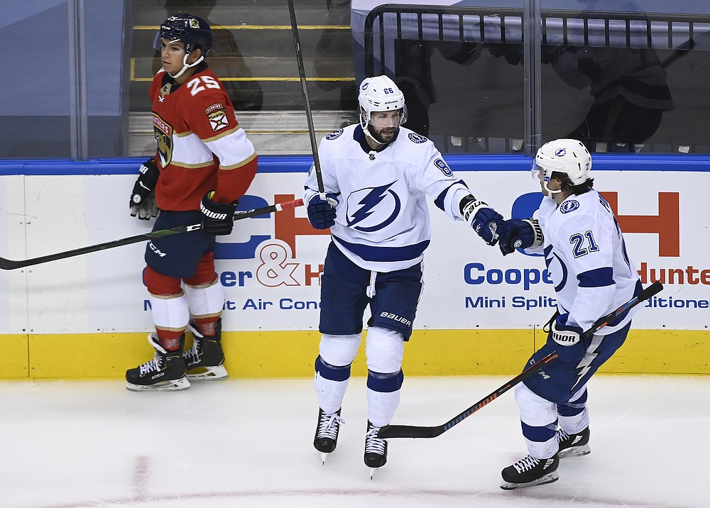 Tampa Bay Lightning right wing Nikita Kucherov (86) celebrates his goal with teammate Brayden Point (21) as Florida Panthers defenseman Brady Keeper (25) looks on during the third period of an exhibition NHL hockey game ahead of the Stanley Cup playoffs in Toronto on Wednesday, July 29, 2020.  (Nathan Denette/The Canadian Press via AP)