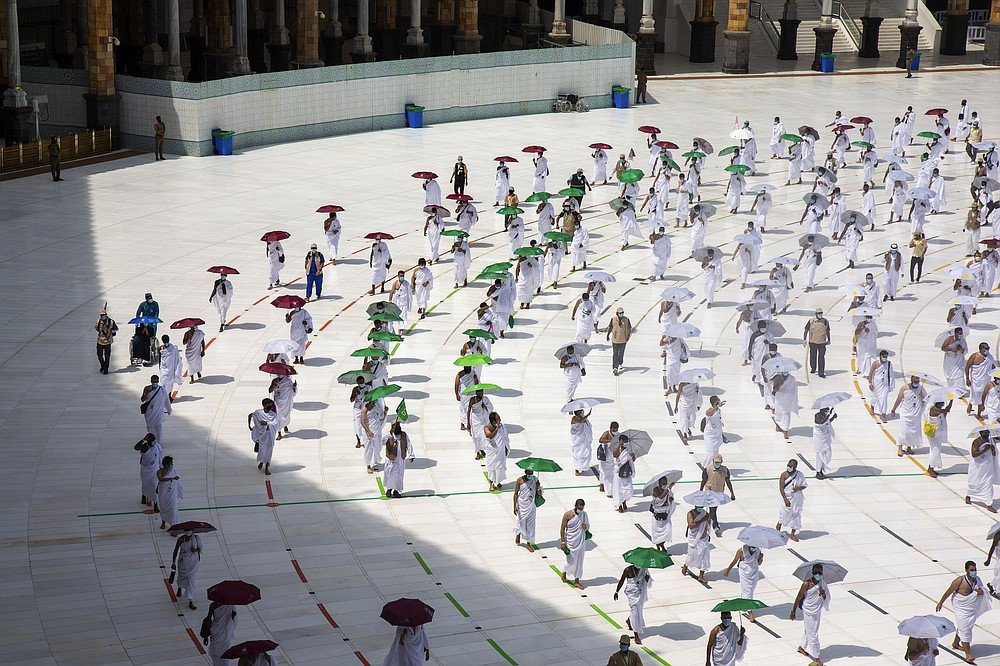 In this photo released by the Saudi Media Ministry, a limited numbers of pilgrims move several feet apart, circling the cube-shaped Kaaba in the first rituals of the hajj, as they keep social distancing to limit exposure and the potential transmission of the coronavirus, at the Grand Mosque in the Muslim holy city of Mecca, Saudi Arabia, Wednesday, July 29, 2020. The hajj, which started on Wednesday, is intended to bring about greater humility and unity among Muslims. (Saudi Media Ministry via AP)