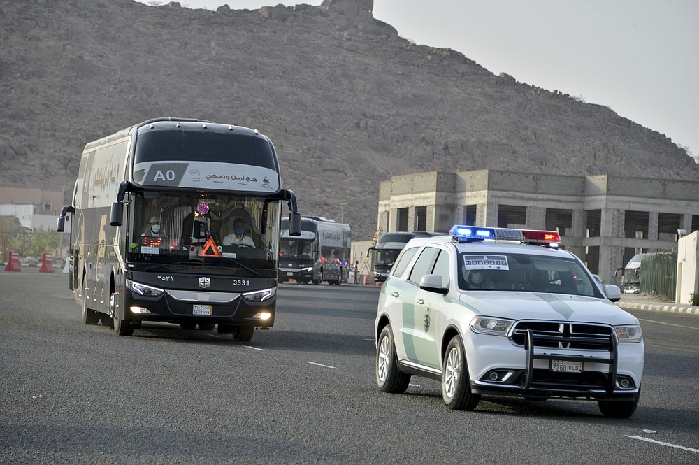 A police vehicle escorts a pilgrim convoy as they move towards the Grand Mosque ahead of the Hajj pilgrimage in the Muslim holy city of Mecca, Saudi Arabia, Wednesday, July 29, 2020. During the first rites of hajj, Muslims circle the Kaaba counter-clockwise seven times while reciting supplications to God, then walk between two hills where Ibrahim's wife, Hagar, is believed to have run as she searched for water for her dying son before God brought forth a well that runs to this day. (AP Photo)