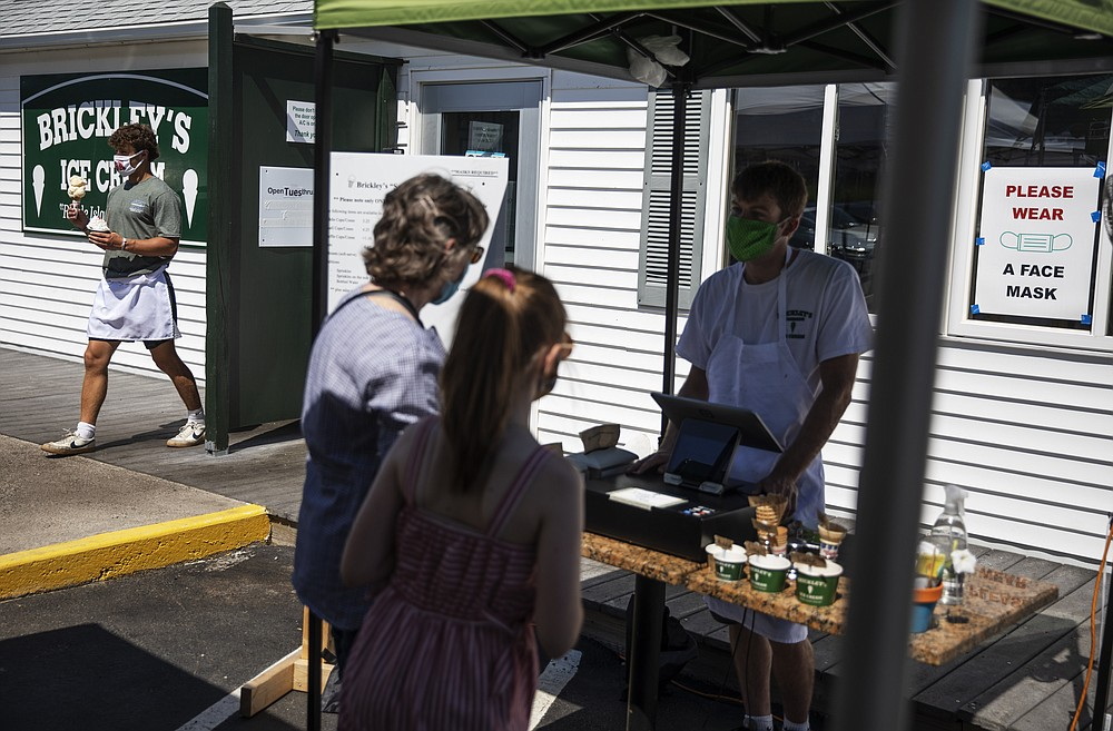 Employees serve customers with masks at a Brickley's Ice Cream shop, one of two stores, in Narragansett, R.I., Wednesday, July 29, 2020. The other nearby location closed when teenage workers were harassed by customers who refused to wear a mask or socially distance. Disputes over masks and mask mandates are playing out at businesses, on public transportation and in public places across America and other nations. (AP Photo/David Goldman)