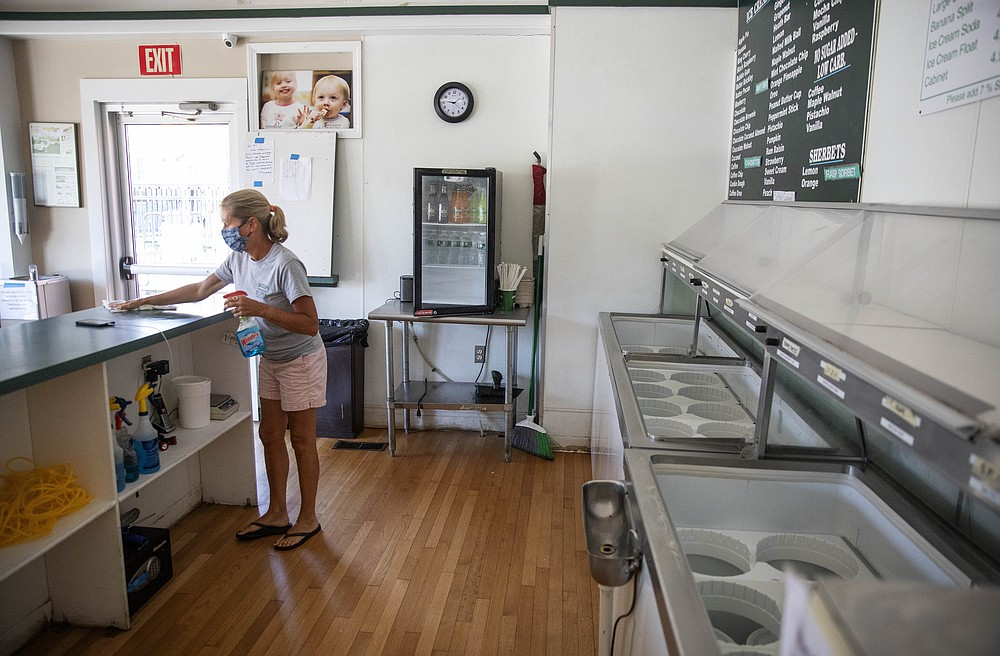 Chris Brophy cleans one of two Brickley's Ice Cream shops she owns with her husband which they closed for the season after teenage workers were harassed by customers who refused to wear a mask or socially distance, in Wakefield, R.I., Wednesday, July 29, 2020. Disputes over masks and mask mandates are playing out at businesses, on public transportation and in public places across America and other nations. (AP Photo/David Goldman)