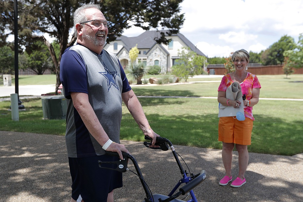 Stephen Donelson, left, smiles as he walks up his driveway to his home accompanied by his wife, Terri, in Midlothian, Texas on Friday, June 19, 2020, after his 90-day stay in the Zale Hospital on the UT Southwestern Campus. Donelson's family hadn't left the house in two weeks after COVID-19 started spreading in Texas,hoping to shield the organ transplant recipient. Yetone night, his wife found him barely breathing, his skin turning blue,and called 911. (AP Photo/Tony Gutierrez)