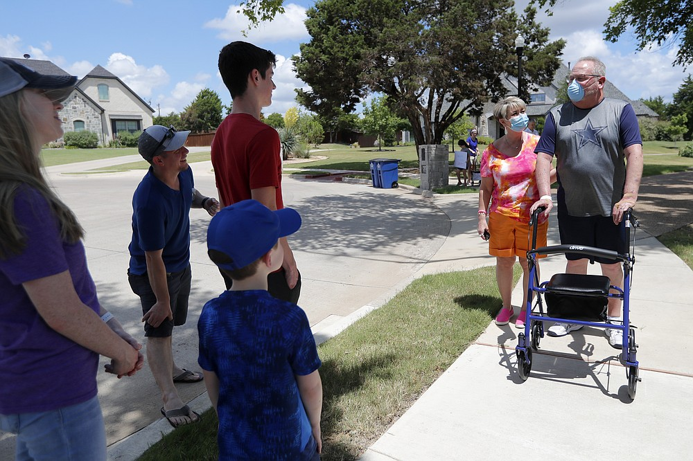 Terri Donelson and her husband, Stephen, right, are greeted by friends, family and neighbors after his arrival at his home in Midlothian, Texas on Friday, June 19, 2020. A trick doctors around the world shared with each other: Flip COVID-19 patients over from their backs to their stomach. It's called proning and it takes pressure off the lungs, which lie closer to the back. Donelson stayed on his belly about 16 hours a day early on, as his doctors watched his oxygen levels improve. (AP Photo/Tony Gutierrez)