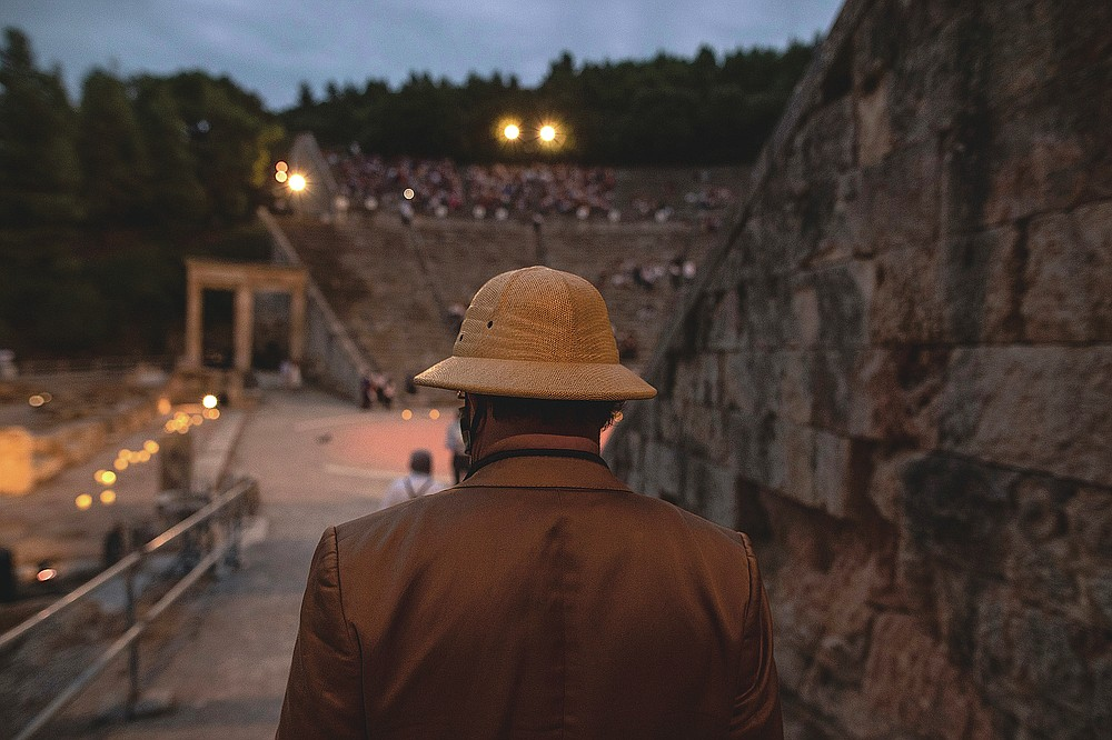 A man enters the ancient theater of Epidaurus, Greece, on Friday, July 17, 2020, to listen a solo concert by Greek violinist Leonidas Kavakos. Live concerts and events have been mostly canceled in Greece this summer due to pandemic concerns. But the Culture Ministry allowed the ancient theaters of Epidaurus in southern Greece and Herodes Atticus in Athens to host performances under strict safety guidelines.(AP Photo/Petros Giannakouris)