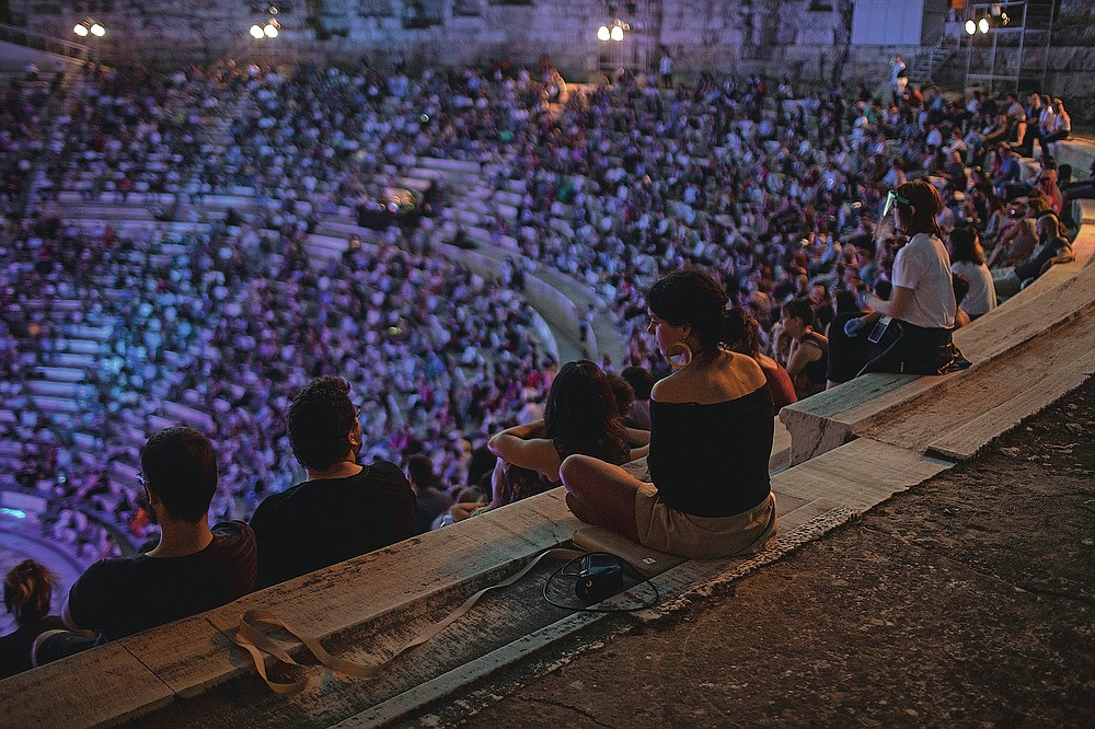 Spectators listen a concert at the Odeon of Herodes Atticus in Athens, on Wednesday, July 15, 2020. The ancient theaters of Herodes Atticus in Athens and Epidaurus in the southern Peloponnese area have reopened for performances with strict seating limits and public health safety guidelines. (AP Photo/Petros Giannakouris)